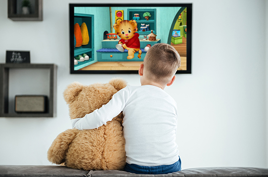 Child watching Daniel Tiger with a stuffed bear